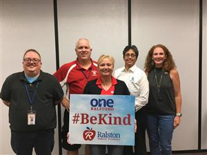 Image of RPS Board of Education holding Be Kind sign
