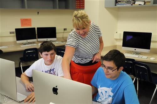 This is a photo of a Ralston High School teacher working with students.