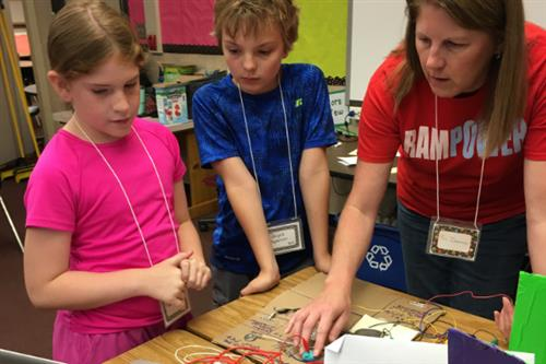 This is a teacher working with students on a circuitry lab.