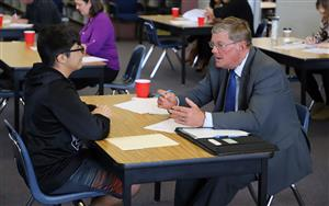 This is a picture of a student and business leader working together on a mock-interview.