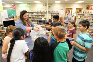 This is an image of a Seymour Elementary teacher working with students at the school's Maker Space.
